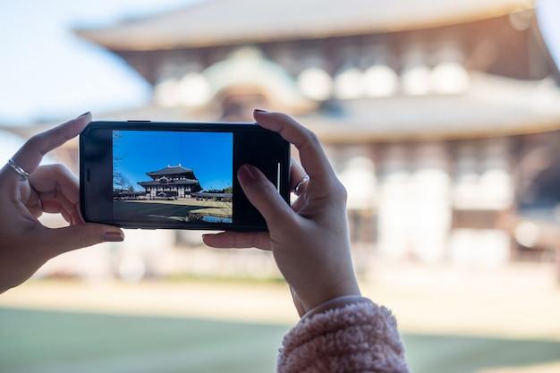 東大寺でスマートフォンで写真を撮る女性