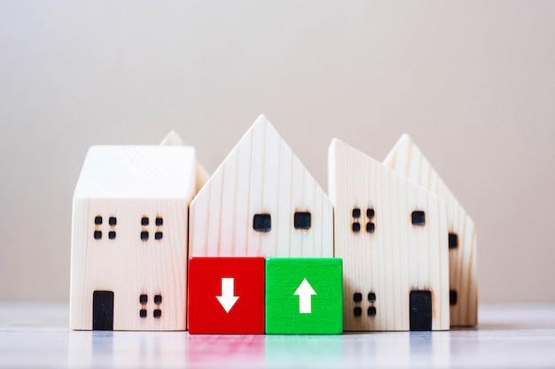 Финансовые блоки куба с деревянной моделью дома на предпосылке таблицы.