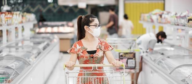 Женщина, носящая защитную маску и делающая покупки в продуктовом магазине или универмаге