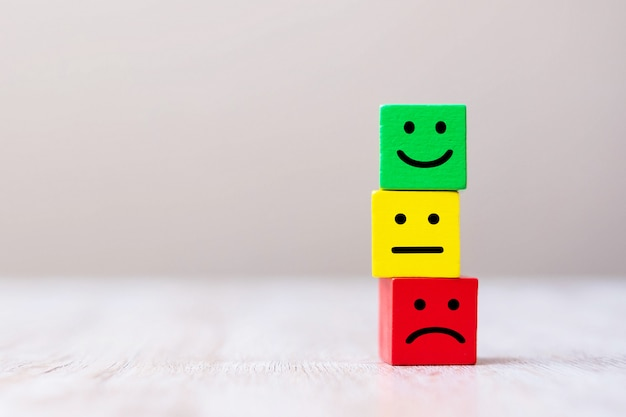木製キューブブロックの感情面記号。サービスの評価、ランキング、顧客レビュー、満足度、フィードバックの概念。