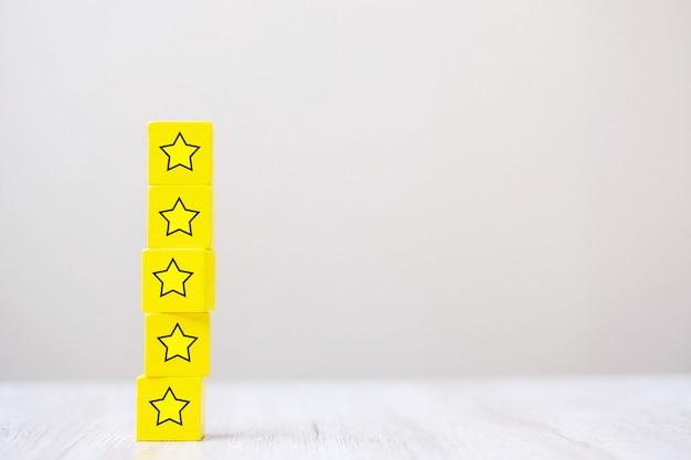 星のシンボルを持つ木製のブロック。カスタマーレビュー、フィードバック、評価、ランキング、サービスコンセプト。