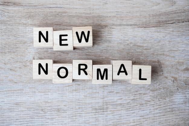 Новые нормальные кубические блоки на фоне стола, конец пандемии коронавируса. поведение человека в образе жизни изменится, например, с использованием маски для лица, личной гигиены