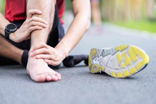 Молодой взрослый мужчина с его мышечной болью во время бега