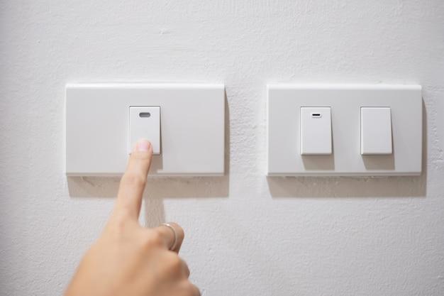 女性の指が自宅の白い壁のライトスイッチをオンまたはオフになっています。省エネ、電力、電気、ライフスタイルのコンセプト。