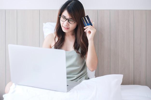 Женщина держа кредитную карточку и используя компьтер-книжку компьютера для онлайн покупок пока делающ заказы на кровати в утре дома.