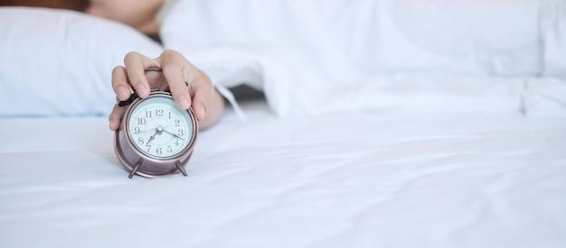 Будильник и азиатская женщина вручают время остановки в кровати пока спящ, молодая взрослая женщина просыпается поздно утром. свежий отдых, сонливость и приятный день