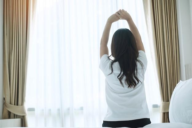 Счастливая женщина растяжения в постели после пробуждения, молодой взрослая женщина поднимая руки и глядя в окно утром. свежий отдых и приятный день концепции
