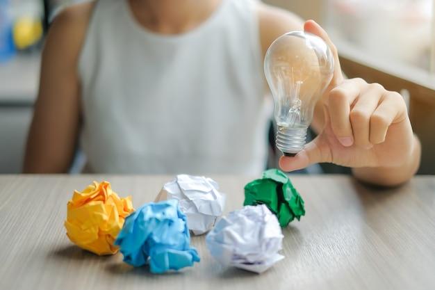 ビジネスの女性電球やランプを持って、カラフルな朱色の紙