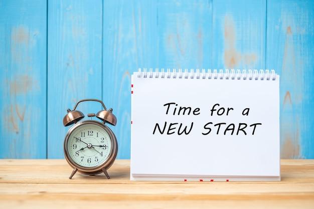 ノートブックとレトロ目覚まし時計の新しいスタートテキストの時間