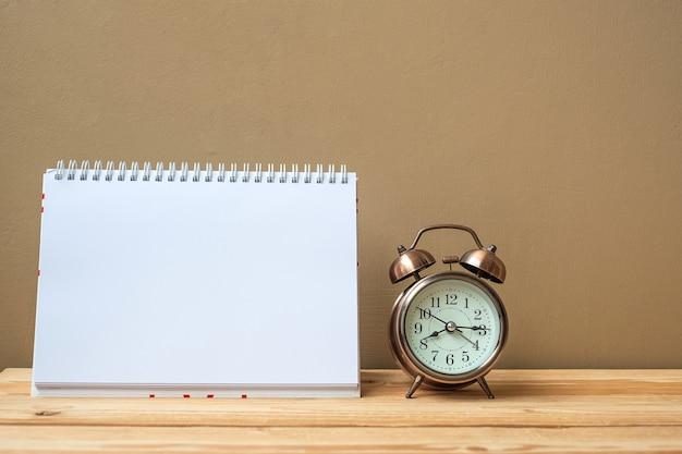 ノートブック、レトロな目覚まし時計、テーブルとコピースペース。目標、ミッション、新しいスタートコンセプト