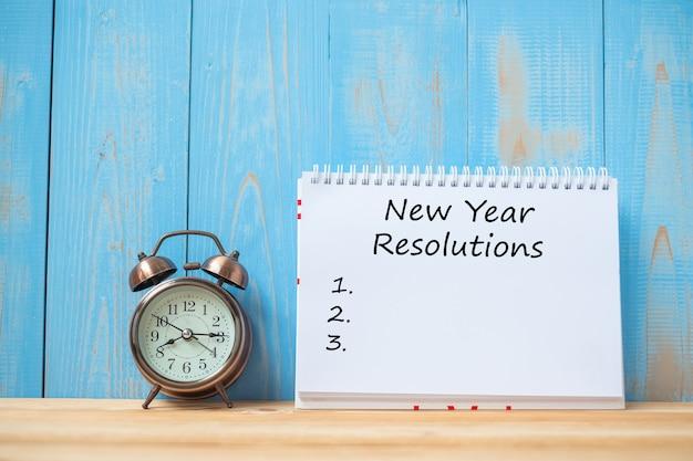 新しい年テーブル上のノートブックとレトロ目覚まし時計の解像度のテキスト