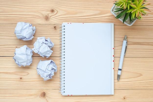 ノートブック、砕けた紙、ペン、テーブル