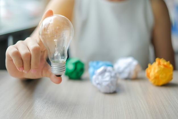 ビジネスの女性電球やランプをカラフルな朱色の紙でつかむ手