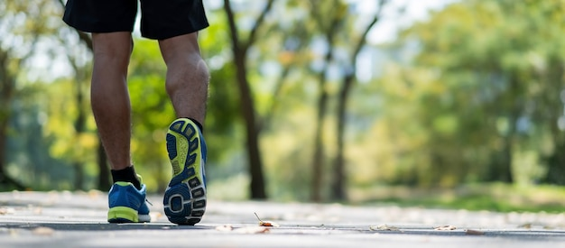屋外の公園で歩く若いフィットネスマンの足