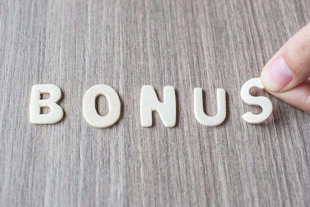 Бонус слово деревянных букв алфавита. концепция бизнеса и идей