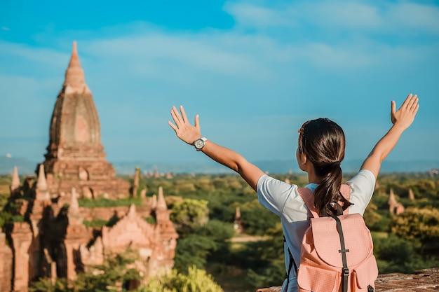 Азиатский путешественник стоит на пагоде и смотрит красивые древние храмы, баган, мьянма