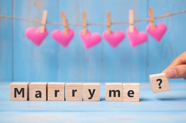 Выходи за меня? деревянные кубики с розовым сердцем формы украшения на синем фоне стола и копирования пространство для текста. любовь, романтика и с днем святого валентина концепция праздника
