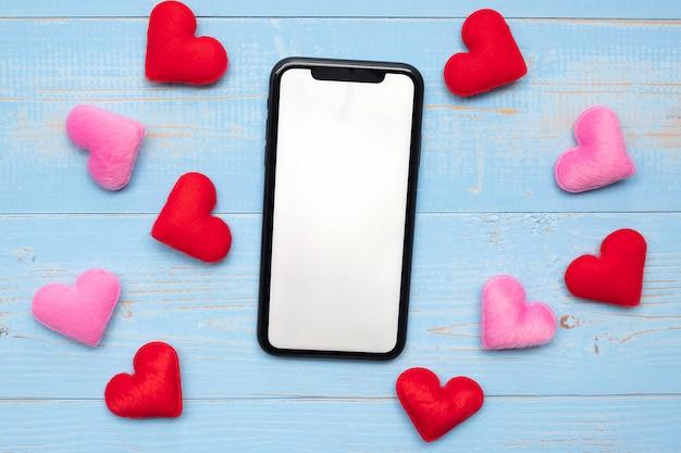 赤とピンクの心を持つ黒いスマートフォンの空白のタッチスクリーンディスプレイは、青い木製のテーブル背景に装飾を形作ります。