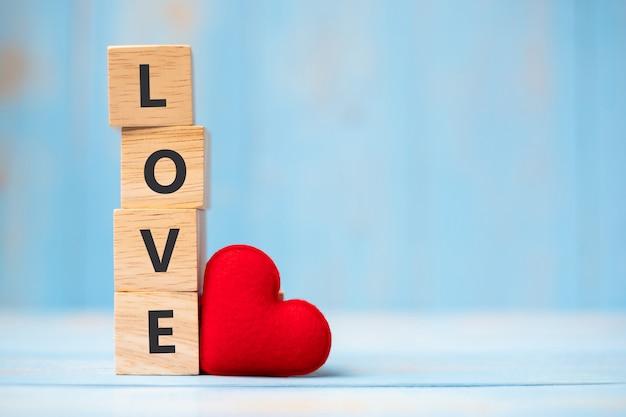 Любовь деревянные кубики с красным украшением в форме сердца на синем фоне стола