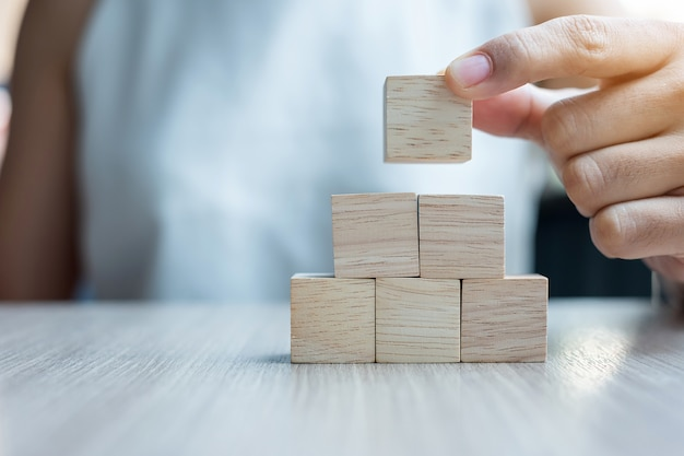 手が建物に木のブロックを配置または引っ張る。