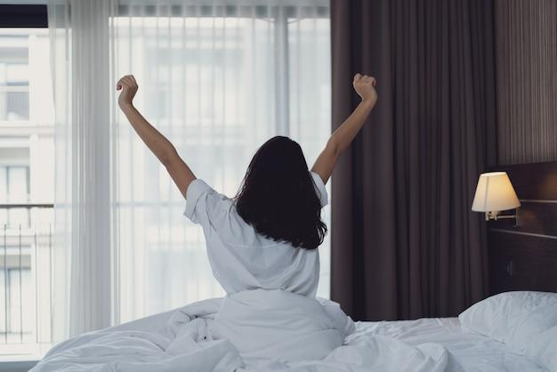 午前中に寝室で若い女性。ベッドに座っている女の子