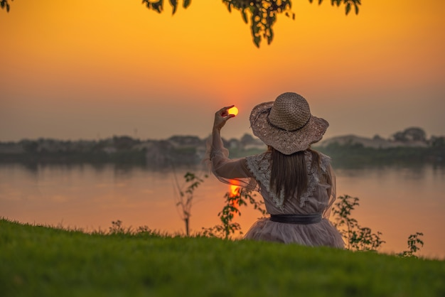 少女は夕日を楽しんで座っています。女性が太陽を捕まえる