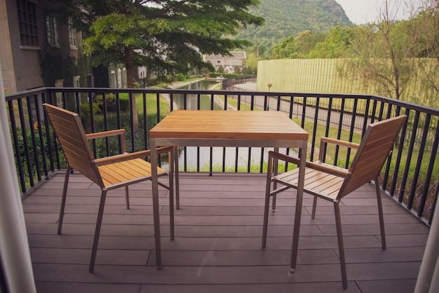家のバルコニーに設置された木製のテーブルと椅子