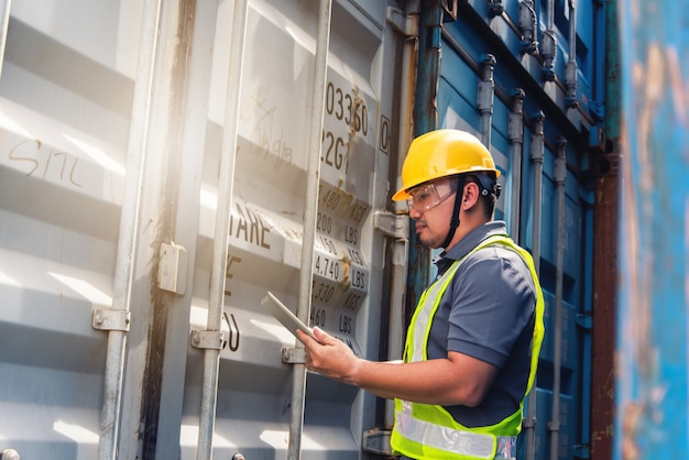 Инженер осматривает контейнер. бизнес логистическая концепция, концепция импорта и экспорта
