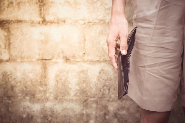 空の黒い財布を持っている男の手のクローズアップ