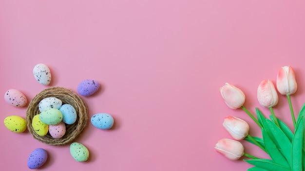 ハッピーイースター、イースターエッグとピンク色の背景にチューリップの花のトップビュー