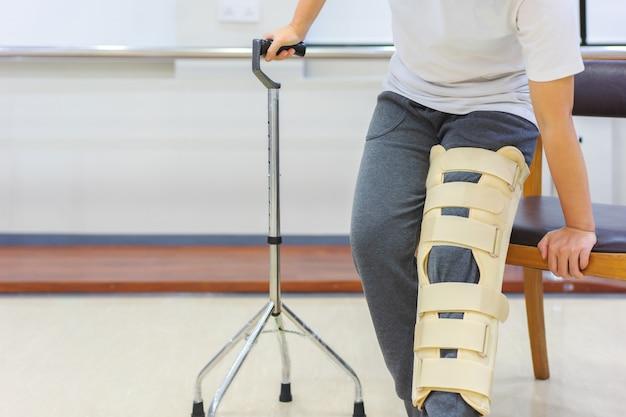女性患者は椅子から起き上がるのに杖を使用している間動きを減らすために膝支持装置を着用します。