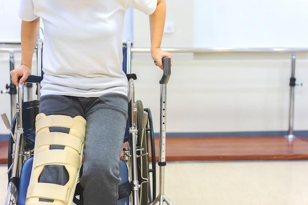 女性患者は車椅子から起きている間動きを減らすために膝サポート装置を身に着けている。