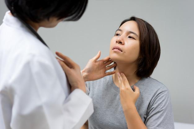 医師は女性患者の負傷した首を調べています