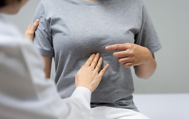女性医師は診療所内のベッドに座っている女性患者の腹部触診によって検査しています。