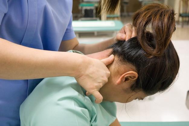 理学療法士は女性患者のために痛みを訴えている