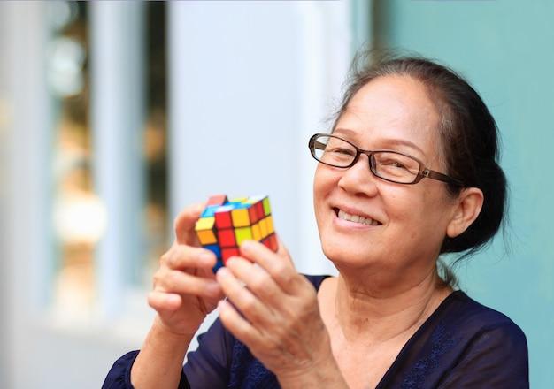 アジアの年配の女性が遊ぶか、ルービックキューブゲームを解きます。