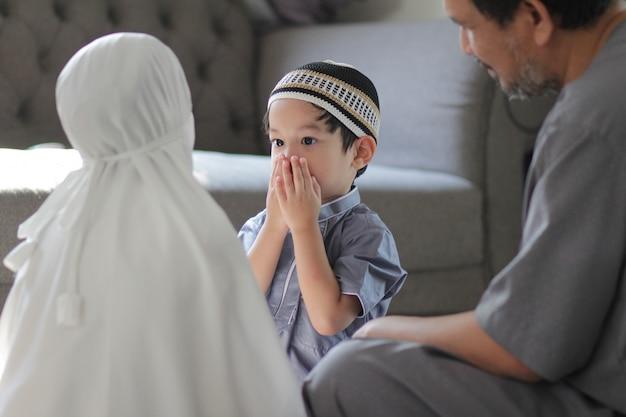 伝統的な衣装を着たアジアのイスラム教徒の家族。神に祈った後、家に子供がいるイスラム教徒の父。ラマダンの聖なる月のイスラム教徒の人々の概念。