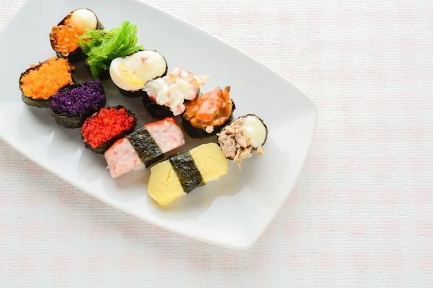 白い皿に寿司、マグロ、サーモン、スズキ、甘い卵、海老寿司、日本食