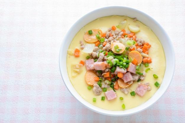 Кухня с заварным кремом на пару в белой миске с рубленой свининой, колбасой и беконом