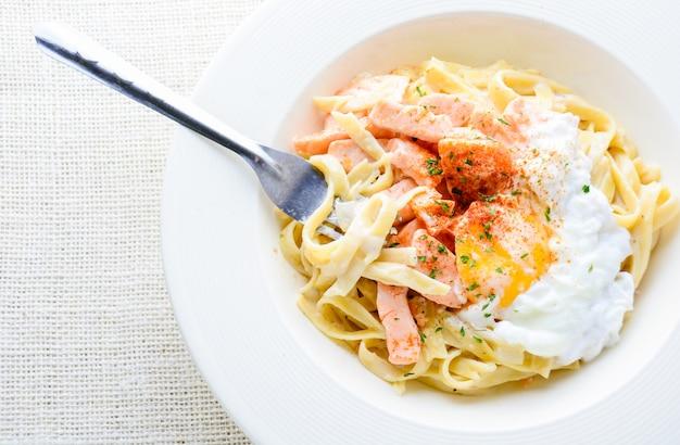サーモン、卵、パルメザンチーズのフェットチーネ、白いプレートで提供しています。