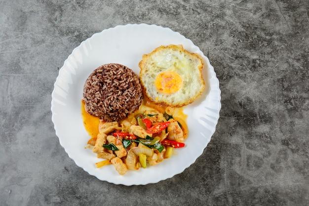 鶏肉の甘い玉ねぎとピーマンを炒め、玄米と目玉焼きを白い皿に添えて