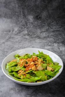 炒めた雪豆とベトナム風ポークソーセージを炒め、シャキッとした揚げたエシャロットとニンニクをトッピング