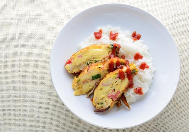Нарезанный омлет с мягким тофу, крабовой палочкой и зеленым луком с рисом на блюде