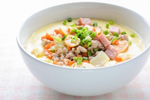 Кухня с заварным кремом на пару в белой миске с рубленой свининой