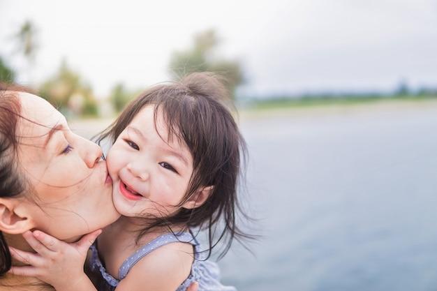 ビーチの背景で娘と一緒に美しい若い母親