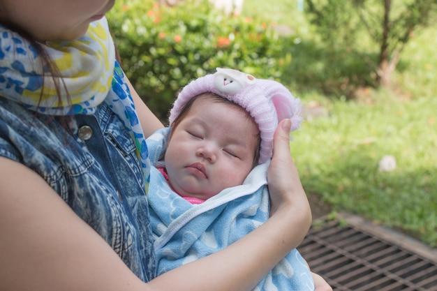 公園で眠っている赤ちゃんを持つ母親。