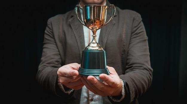 Бизнесмен празднует с трофеем за успех в бизнесе