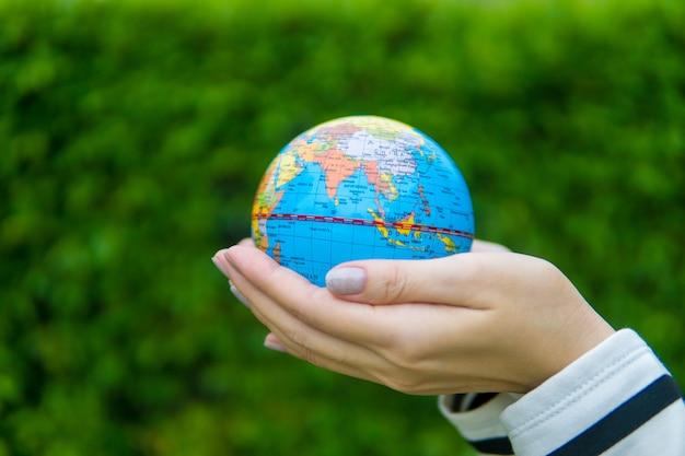 緑色の背景で地球と女性の手。