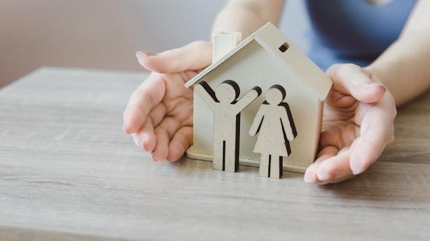 家族の手で木製のモデルハウスを保持している女性