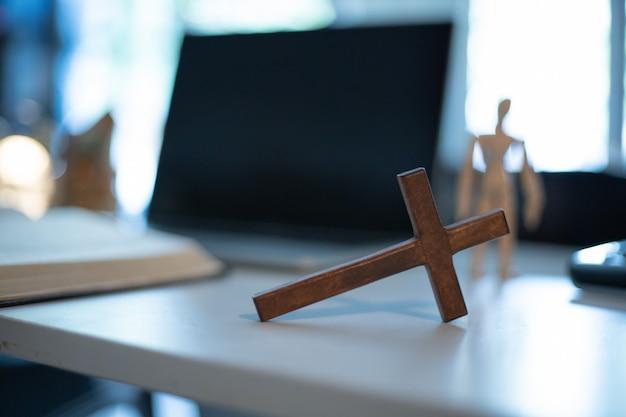 窓の光で木のテーブルを渡ります。オンライン教会の概念。